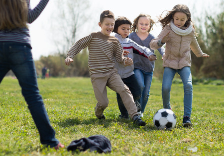 active girls and boy playing soccer in park in autumn Stock Photo