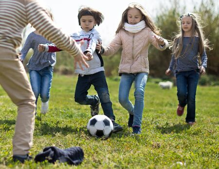 girls and a boy playing soccer funny in park in autumn Stock Photo