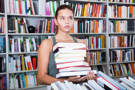 english ethnicity: teenager girl brunete looks for the right book in library