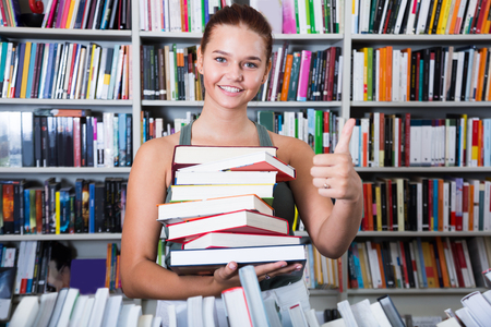 brunete: smilling teenager girl holding a stack of books in bookstore