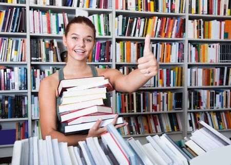 teenager girl holding stack of books shows thump up in a bookstore