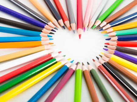 Colored pencils lying around the heart on white background Stock Photo