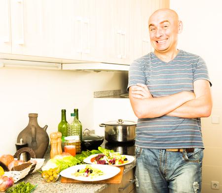 happy smiling man in the prime of life in kitchen prepared two salads 版權商用圖片