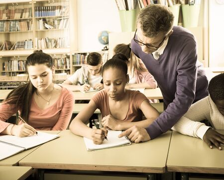 the elderly tutor: male teacher helping African-American pupil in classroom Stock Photo