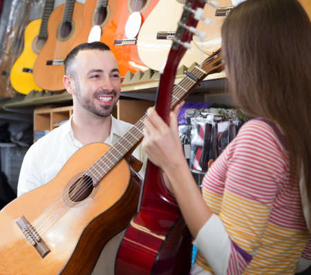 Positive young couple buying new guitar in store and smiling Stock Photo