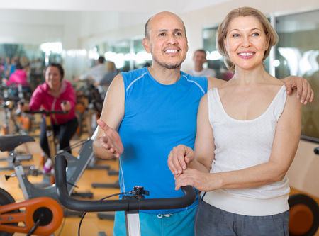positive mature couple posing in the gym
