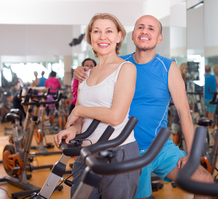 smiling mature man and woman in background bikes at the gym Stock Photo