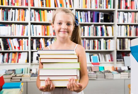 child girl holding a stack of books in a bookstore Stock Photo