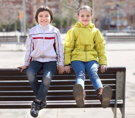 ordinary children posing on street bench in Indian summer Stock Photo
