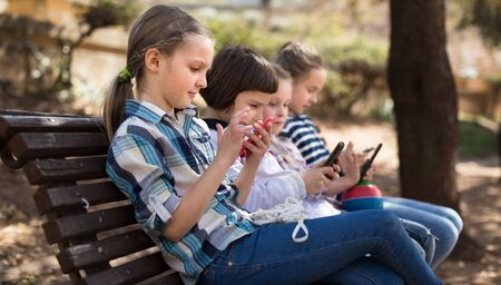 ordinary children playing with the phone on bench outdoors Stock Photo