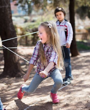 children games. blonde Girl gently goes through the tangled rope Stock Photo