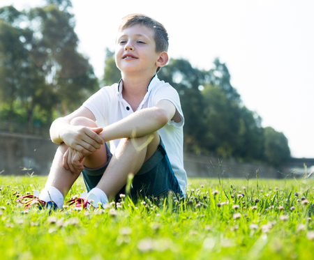 nice boy in shirt sitting on the grass