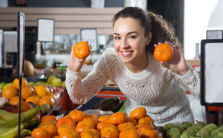 russian ethnicity caucasian: portret of young happy female choosing mandarins at store
