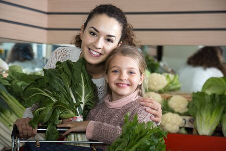 purchasers: smiling mother and blonde daughter buying greenery in shop