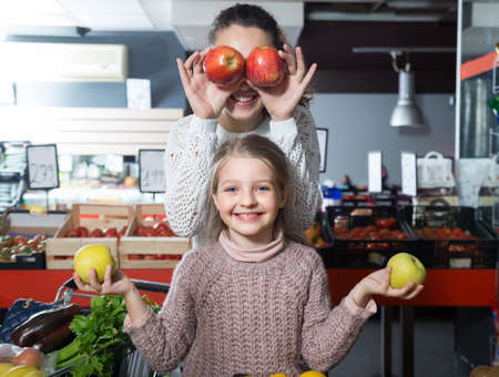 russian ethnicity caucasian: positive woman and lsmiling ittle girl posing whith apples in department fruits of store Stock Photo