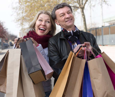 autumnn: Smiling elderly husband and wife spouses with shopping bags in autumnn day Stock Photo