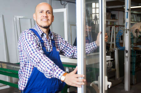 Gestionnaire satisfait approuvant le travail des employés à l'usine de fenêtres en PVC
