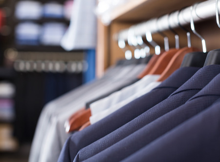 row of luxury jackets on hangers in men clothing store Stock Photo
