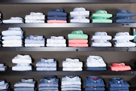 many cotton shirts on shelfs in men clothing store