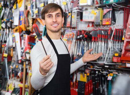Joven vendedor masculino posando en la sección de herramientas de la tienda del hogar Foto de archivo