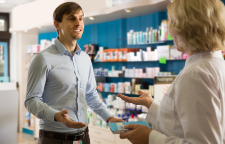 shopper: Young interested man near counter in  drugstore