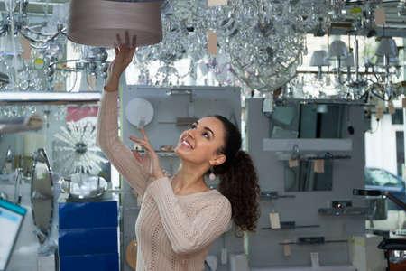 shopper: Ordinary young brunet woman doing shopping in lighting store