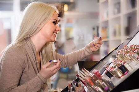 lustre: Positive blonde female customer selecting beauty treatment in makeup section