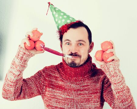 english ethnicity: Portrait of Man on holiday in hat and whistle with tangerines Stock Photo