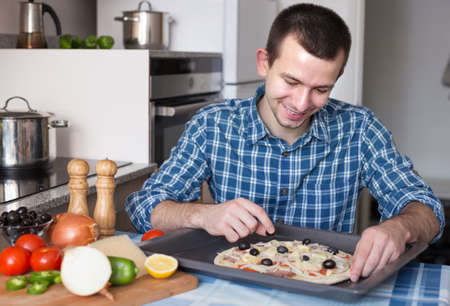 25s: Young man preparing pizza in the kitchen Stock Photo