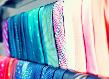 Row of fashion neckties on hangers in men clothing store