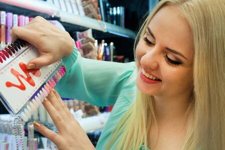 25s: Portrait of woman selecting nail polish in beauty store