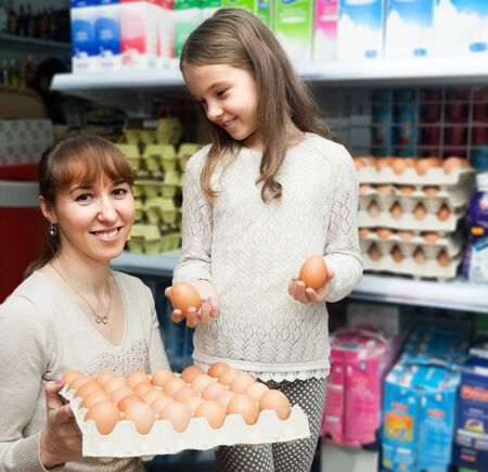 young Woman with little girl choosing selecting eggs at dairy store Stock Photo