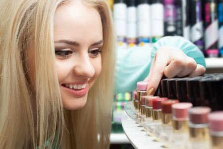 Portrait of smiling young blondie selecting lipstick in shop Stock Photo