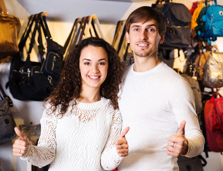 happines: Positive smiling couple in the hanbags shop