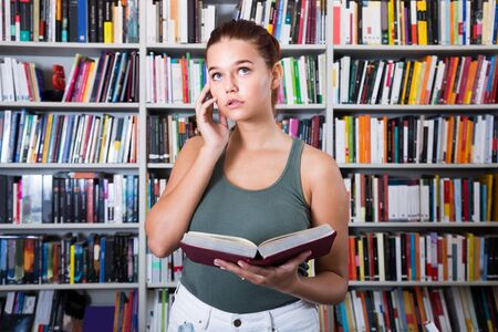 brunete: perplexed brunete girl chooses a book in the library