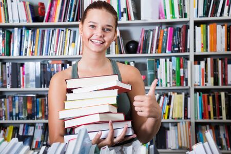 nice teenager girl holding stack of books shows thump up in a bookstore