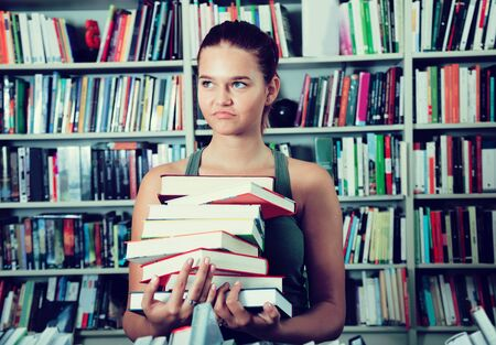 store shelf: brunete girl chooses a book in university library