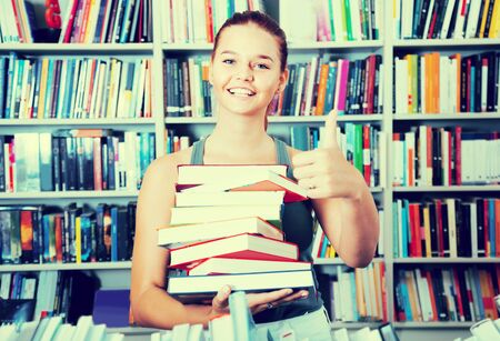 teenager girl holding stack of books shows thump up in a bookstore shows thump up