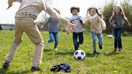 funny Children play with ball outdoors in spring