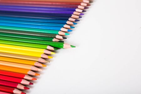 colored pencils lying in row on white background