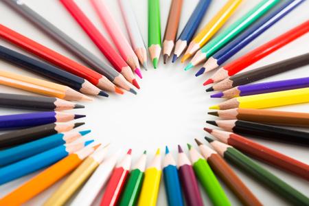 Lápices de colores que mienten alrededor del corazón en el fondo blanco Foto de archivo - 83062605