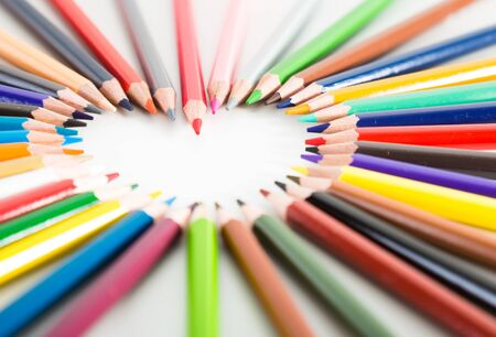 colored pencils lying around the heart on white background