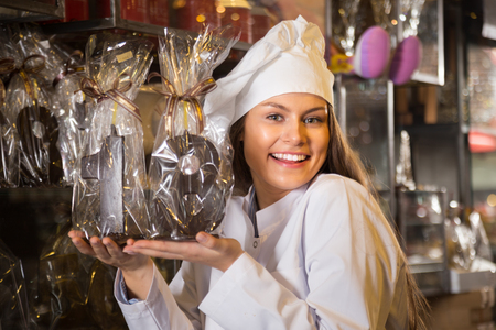 Young ssaleswoman posing with fine chocolate numbers and cakes for sale