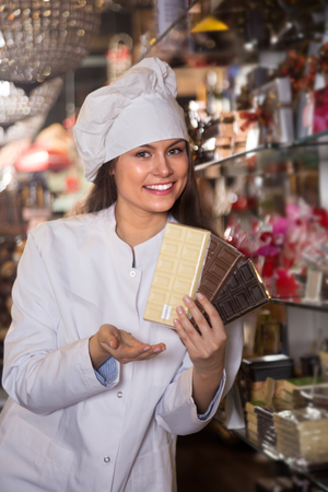 Young woman selling chocolates and confectionery in cafe