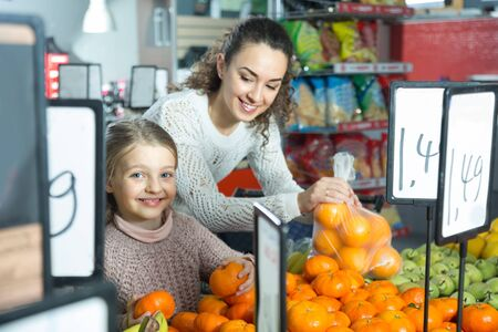 smiling mother and blonde daughter buying mandarins in shop. focus on girl Stock Photo