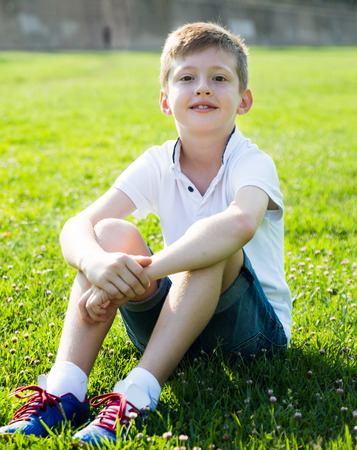Boy in shirt sitting on the grass in park Stock Photo