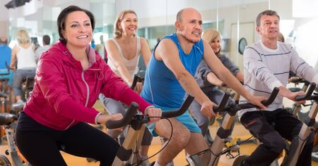 english ethnicity: satisfied older people do sports on exercise bikes. focus on the left woman