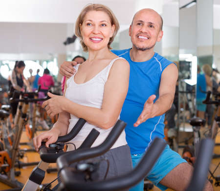 smiling mature couple posing in the gym