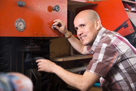 Professional smiling craftsman stitching footwear on machine in shoe atelier Stock Photo