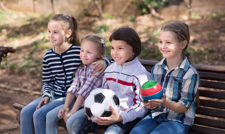 ordinary children with balls in the park on a bench in autumn Stock Photo